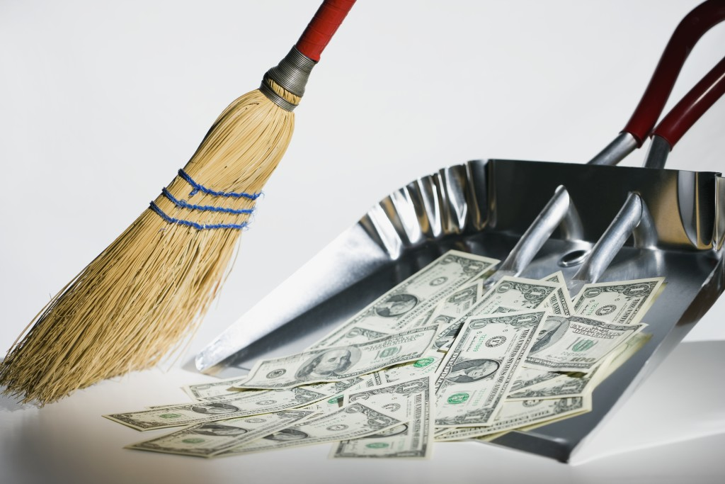 Sweeping US currency into dust pan --- Image by © Steve Hix/Somos Images/Corbis